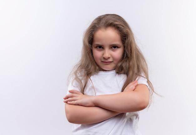 Bambina triste della scuola che indossa la maglietta bianca che attraversa le mani su fondo bianco isolato