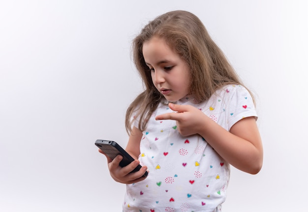격리 된 흰색 배경에 전화에 흰색 티셔츠 포인트를 입고 슬픈 어린 학교 소녀