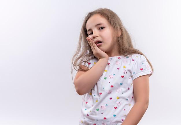 La piccola ragazza triste della scuola che porta la maglietta bianca ha messo la sua mano sul dente dolorante su fondo bianco isolato