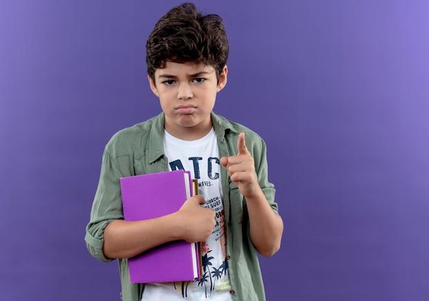 本を持って、コピースペースで紫色の壁に分離されたはいジェスチャーを示す悲しい小さな男子生徒