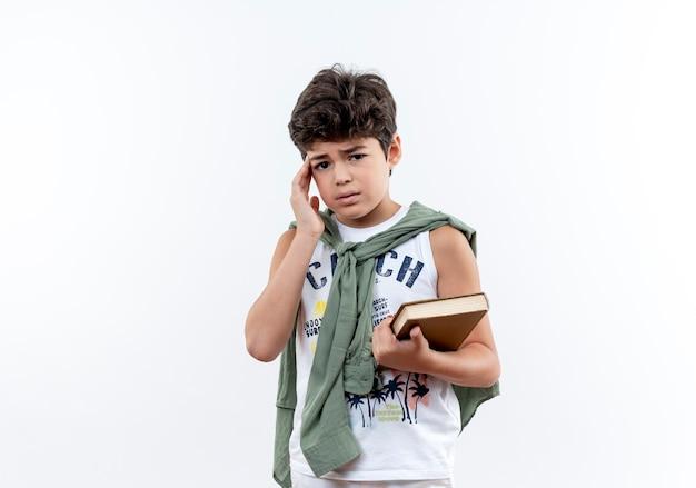Piccolo scolaro triste che tiene il libro e che mette la mano sulla fronte su bianco