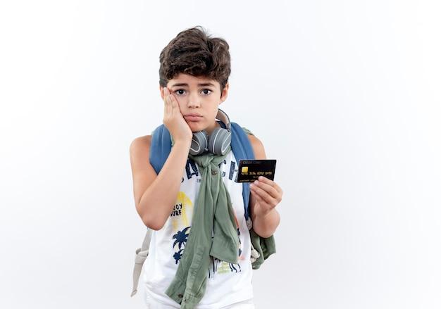 Грустный маленький школьник в сумке на спине и наушниках держит наушники и кладет руку на щеку