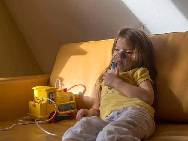 Грустная маленькая больная девочка в пижаме делает ингаляцию сидя на кушетке ребенок болен