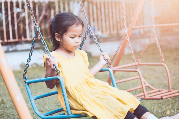 Sad and lonely asian little child girl sitting on swings in playground in vintage color tone