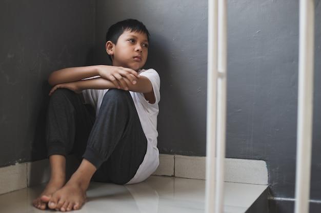 Грустный одинокий мальчик сидит один дома