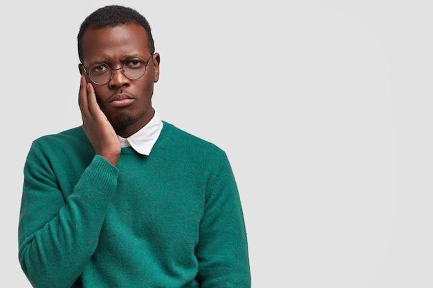 Il giovane nero insoddisfatto e solo triste tiene la mano sulla guancia, si sente dispiaciuto