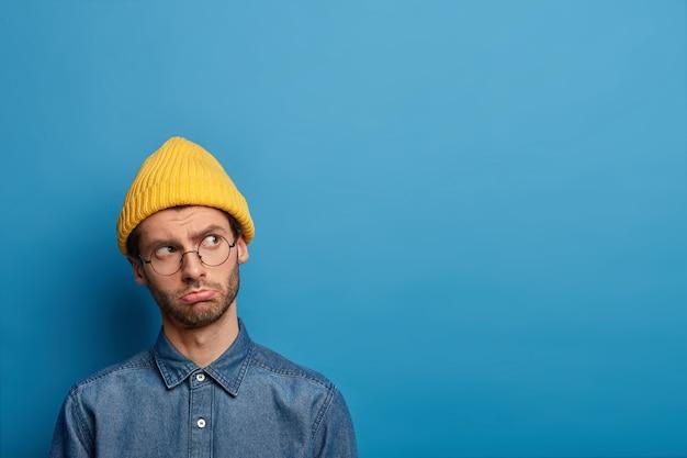 L'uomo triste e solo ha uno sguardo frustrato sul lato destro, pensieri inquieti, indossa occhiali rotondi, cappello giallo e camicia di jeans