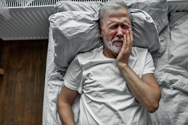 Грустный одинокий старший лежа на кровати в больнице, концепция госпитализации. страдает от болезни, болят зубы, плачет от боли