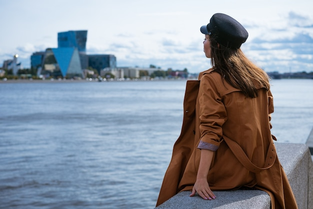 A sad lonely woman in a jacket and a cap sits on the embankment of the river on a gloomy day looks into the distance