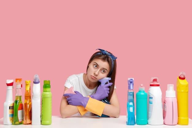 Triste donna sola con un'espressione dispiaciuta, sguardo stanco di stanchezza, trasporta spray per il lavaggio, spugna, vestita con abiti casual