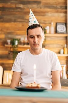 Грустный одинокий молодой человек в праздничной шляпе празднует день рождения в одиночестве, сидит за праздничным тортом и смотрит на него грустными глазами. концепция празднования в одиночку.