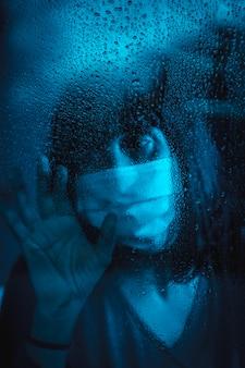 Грустный взгляд молодой кавказской женщины, смотрящей на дождливую ночь в карантине covid19 с маской
