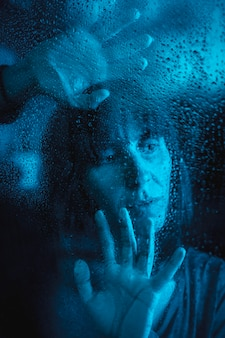 Sad look of a young caucasian woman looking at a rainy night in the quarantine