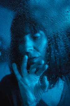 Sad look of a young woman looking at a rainy night in the quarantine of the covid19