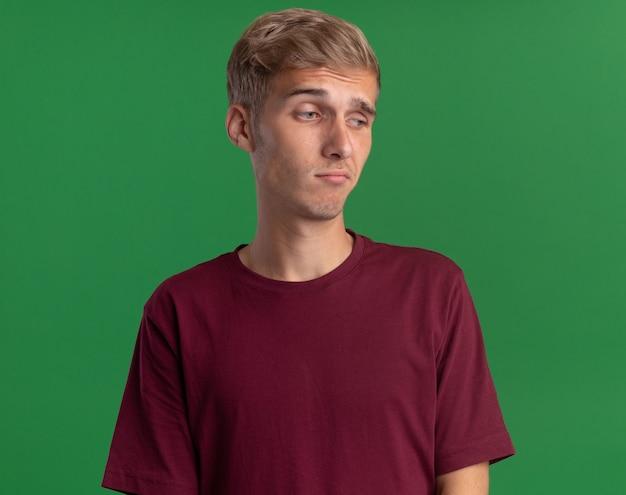 緑の壁に分離された赤いシャツを着て若いハンサムな男を見て悲しい