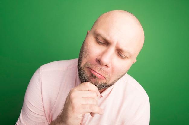Грустно смотрящий вниз лысый мужчина средних лет в розовой футболке схватился за подбородок, изолированный на зеленом