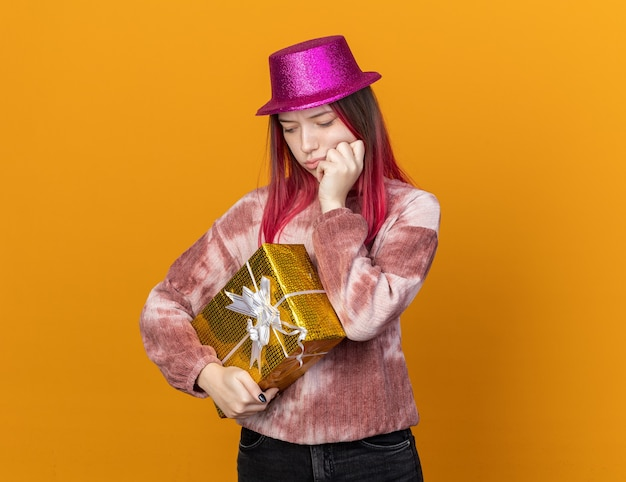 Sad looking down young beautiful girl wearing party hat holding gift box putting hand on cheek