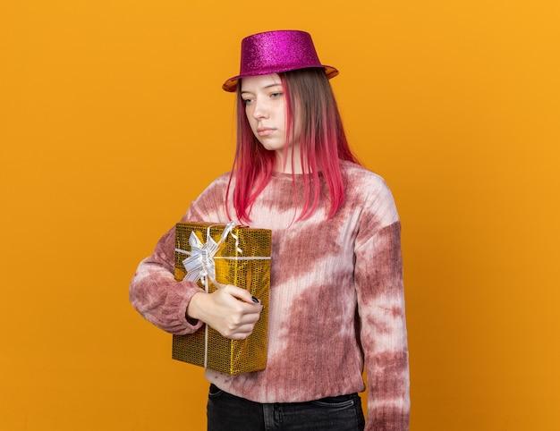 Грустно выглядящая грустная молодая красивая женщина в партийной шляпе держит подарочную коробку, изолированную на оранжевой стене