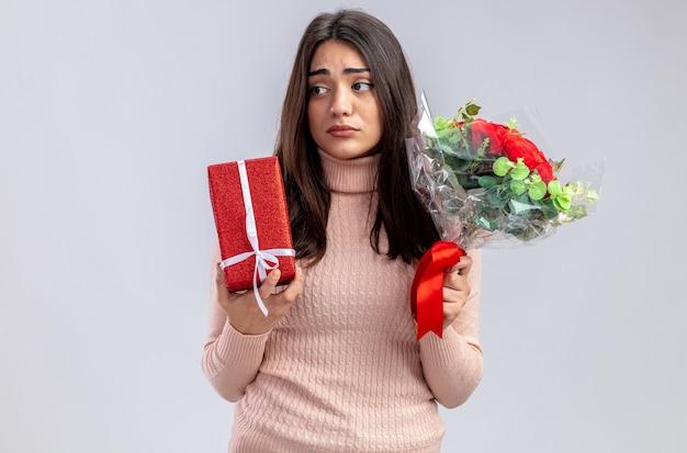 白い背景で隔離の花束とギフトボックスを保持しているバレンタインデーの悲しい探している悲しい少女