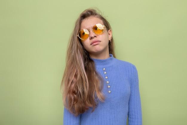 眼鏡をかけている悲しい見ている側の美しい少女