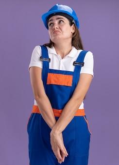 Triste guardando la giovane donna del costruttore in uniforme che si tiene per mano insieme isolata sul muro viola