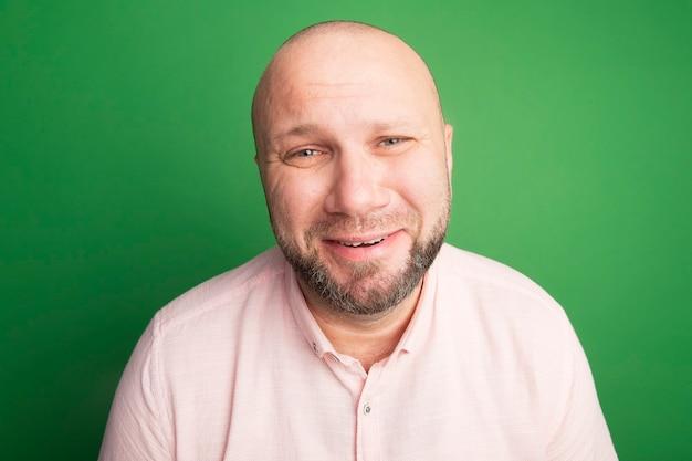 Uomo calvo di mezza età triste guardando dritto davanti a sé che indossa la maglietta rosa isolata sul verde