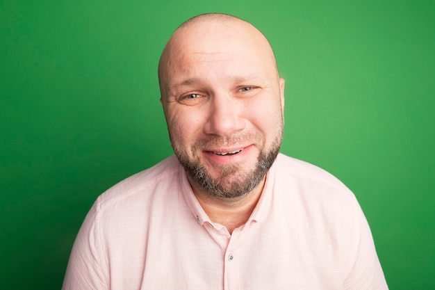 Грустно смотрящий прямо перед собой лысый мужчина средних лет в розовой футболке изолирован на зеленом