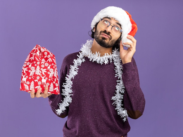 Sad looking up young handsome guy wearing christmas hat with garland on neck holding christmas bag isolated on blue wall