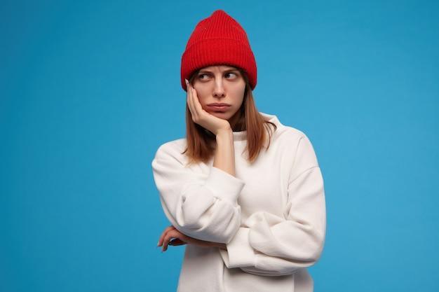 슬픈 찾고 여자, 갈색 머리를 가진 아름 다운 소녀. 흰색 스웨터와 빨간 모자를 쓰고. 그녀의 머리를 손에 대십시오. 지루함을 느낀다. 복사 공간에서 왼쪽으로보고, 파란색 벽 위에 절연