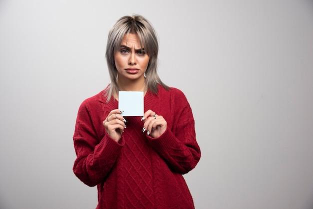 Печально выглядящая женщина, держащая блокнот на сером фоне.