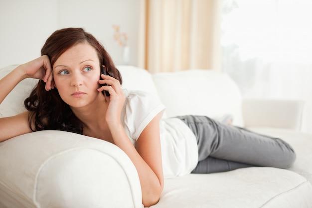소파에 누워 전화에 슬픈 찾고 여자