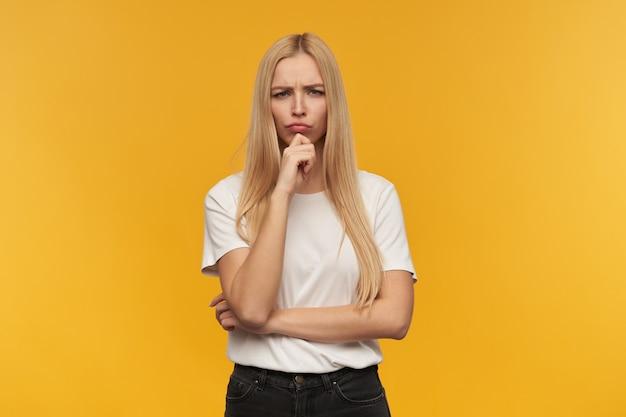 금발의 긴 머리를 가진 슬픈 찾고 여자입니다. 흰색 티셔츠와 검은 색 청바지를 입고 있습니다. 사람과 감정 개념. 오렌지 배경 위에 고립 된 신중하게 카메라를보고