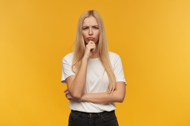 Sad looking woman with blond long hair. wearing white t-shirt and black jeans. people and emotion concept. watching at the camera thoughtfully, isolated over orange background