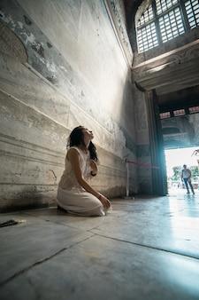 悲しい、失われた希望、少女は神の光の光線にひざまずいて寺院で祈る。