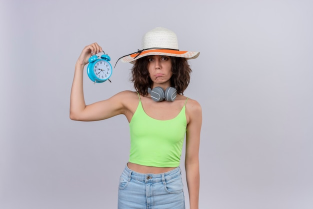 A sad lovely young woman with short hair in green crop top wearing sun hat holding blue alarm clock on a white background