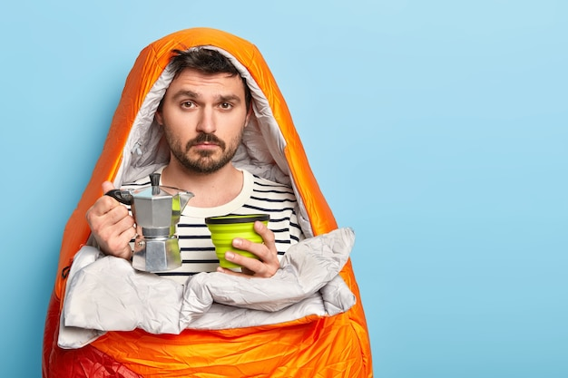 Sad male camper prepares fresh drink, holds coffee pot, spends free time in nature, enjoys summer morning, wrapped in sleeping bag, stands against blue wall