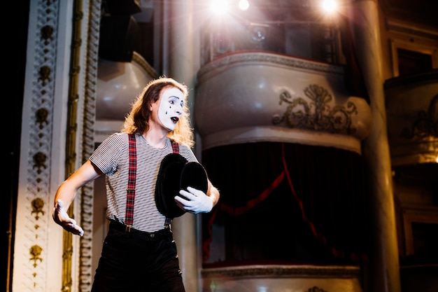 Sad male mime artist rehearsing in the auditorium