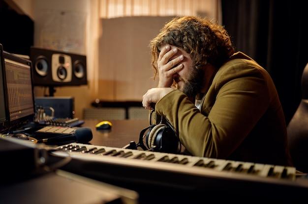 슬픈 남성 사운드 엔지니어, 스튜디오 내부를 배경으로 녹음합니다. 신디사이저 및 오디오 믹서, 음악가 작업장, 창작 과정