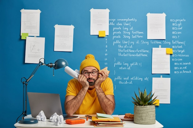 Sad male student preparess to write exam testing, poses at coworking space, holds paper and burger, wears yellow clothes