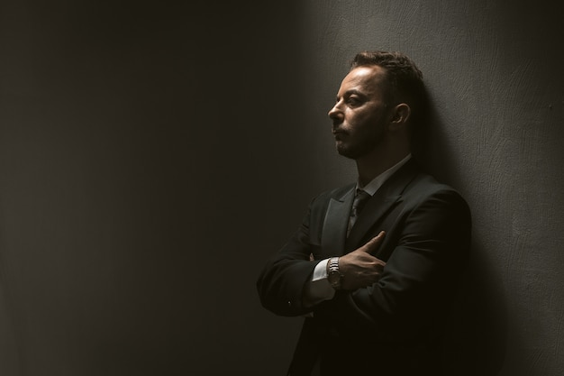 Sad man in black suit on black wall
