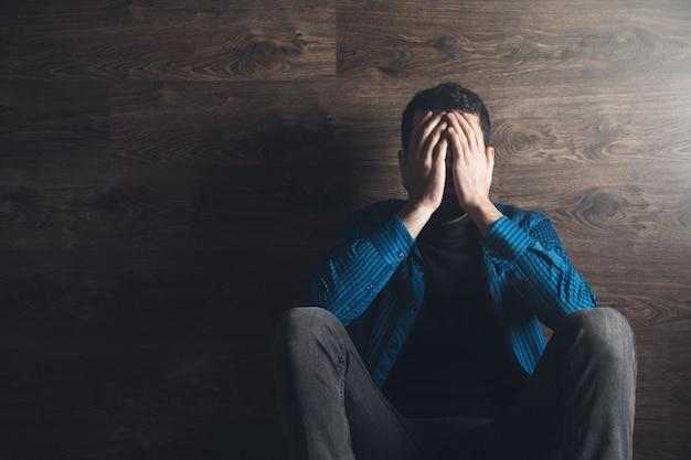 Печальный человек закрыл лицо в темной комнате