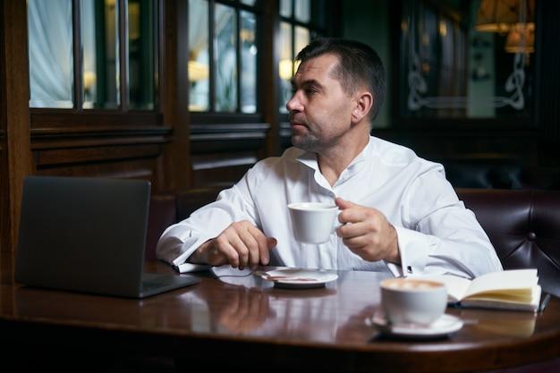 Печальный мужчина пьет кофе в кафе