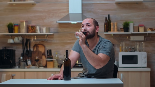 台所で飲んでいる悲しい男。片頭痛、うつ病、病気、不安感に苦しんでいる不幸な人は、アルコール依存症の問題を抱えているめまいの症状で疲れ果てています。