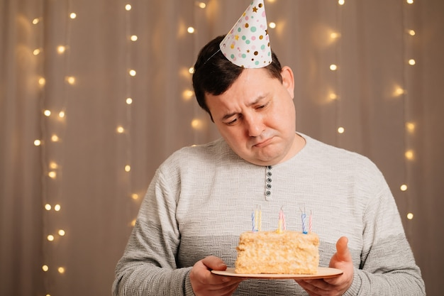 Sad man in a festive cap with a birthday cake blows out candles.