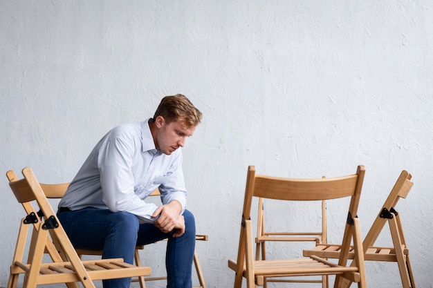Sad man at a group therapy session with empty chairs
