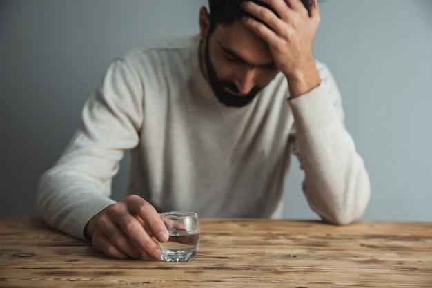 책상에 보드카의 슬픈 남자 손 유리