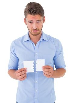 Sad man holding a broken card