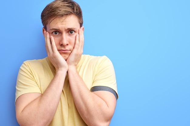 頬を抱えてメランコリックな表情でカメラを見ている悲しい男。孤立した青い背景。カジュアルなtシャツを着た白人の若い男性の肖像画