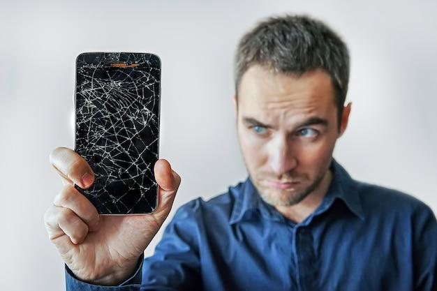Sad man holds broken smartphone. screen broken phone. not working phone