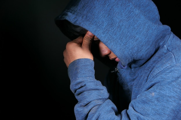 Sad man in hood cover face with hands isolated in black.